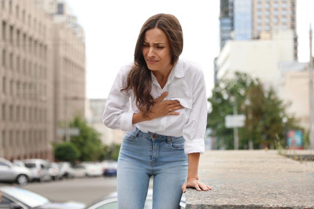 mladá žena sa musela oprieť o múrik a drží sa za srdce s bolesťou v tvári