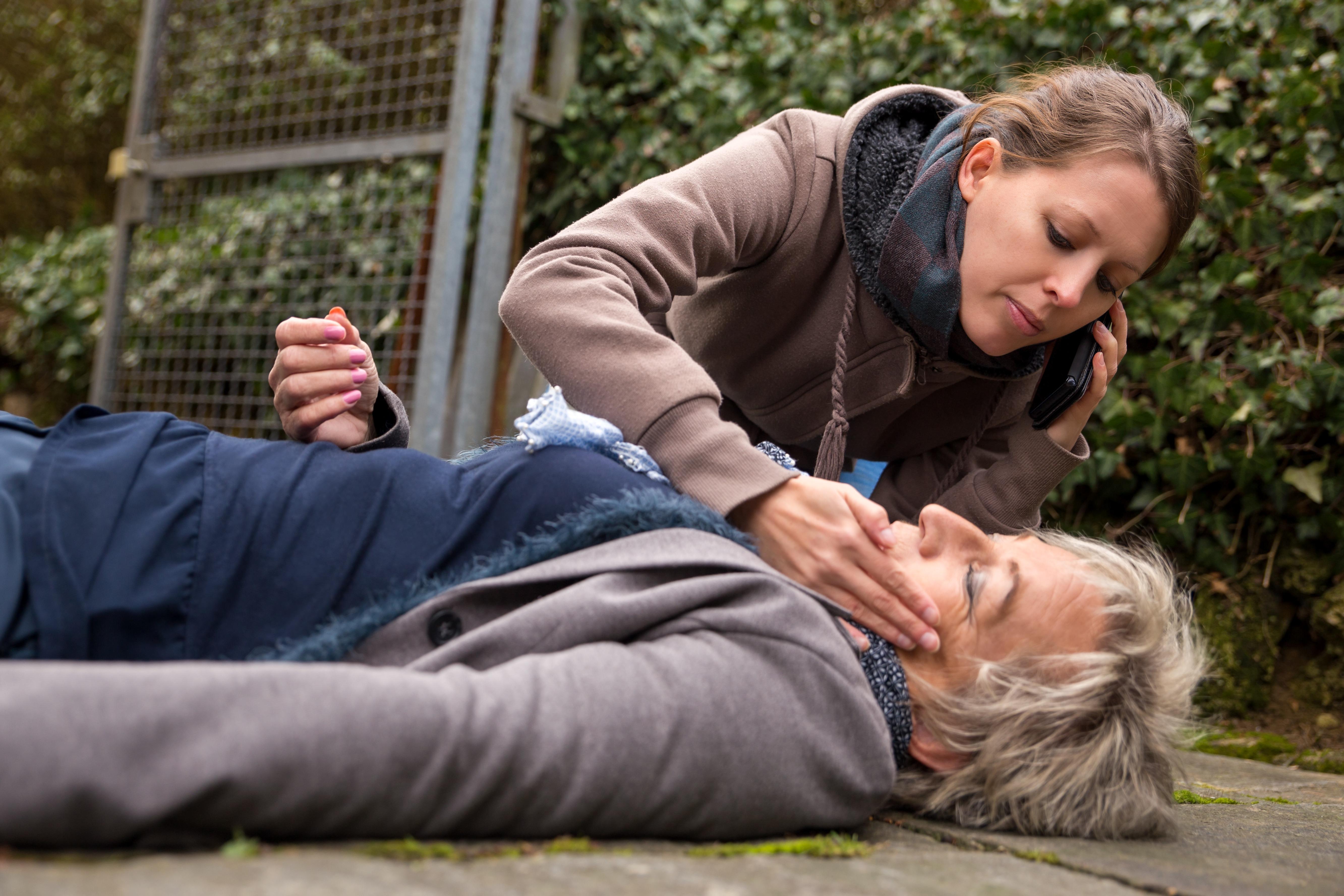 Mladá žena volá záchranku a kontroluje životné funkcie staršej žene ležiacej na zemi v bezvedomí