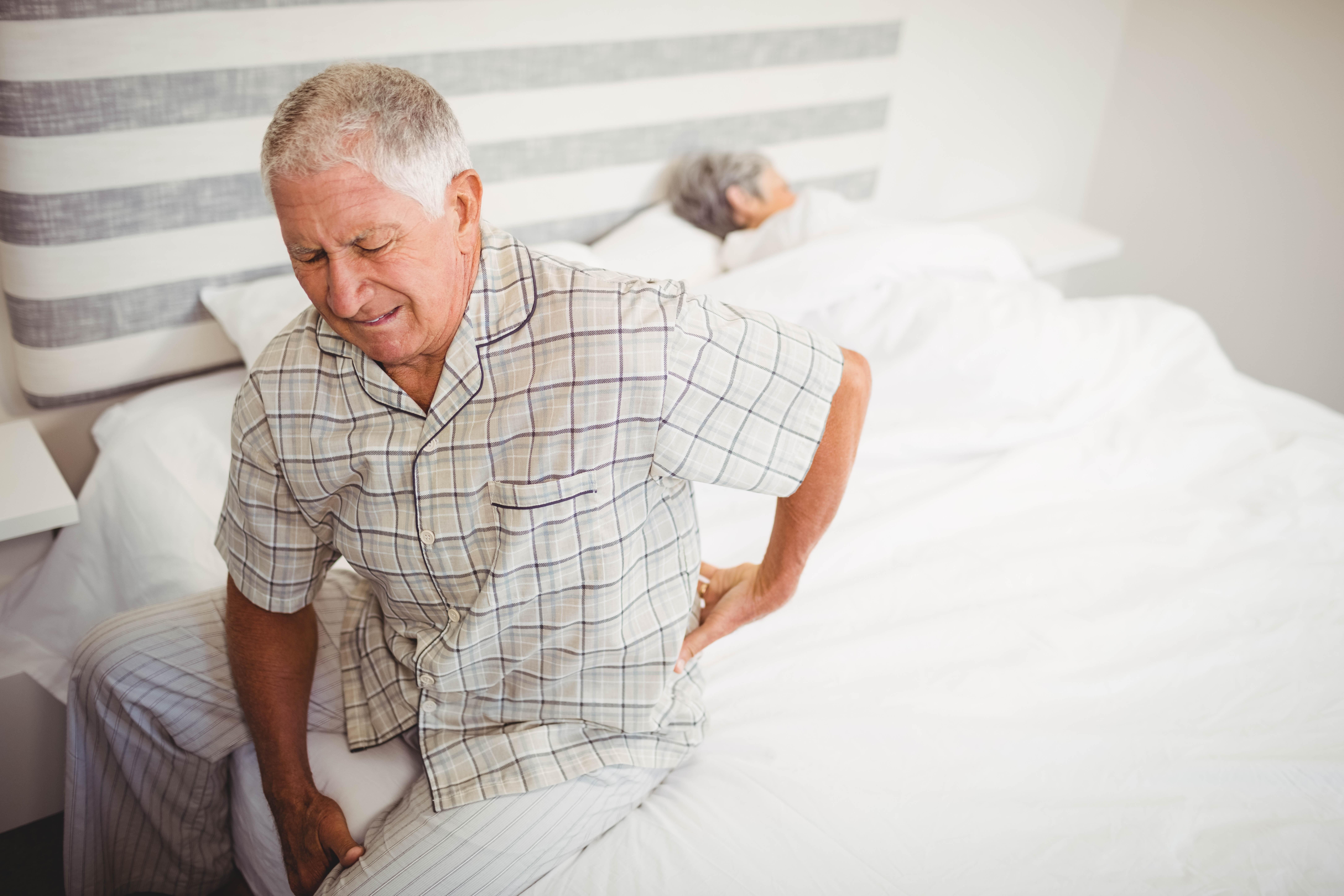 Starý muž vstáva zo svojej manželskej postele s bolesťou v krížoch. Manželka v pozadí spí otočená na druhú stranu
