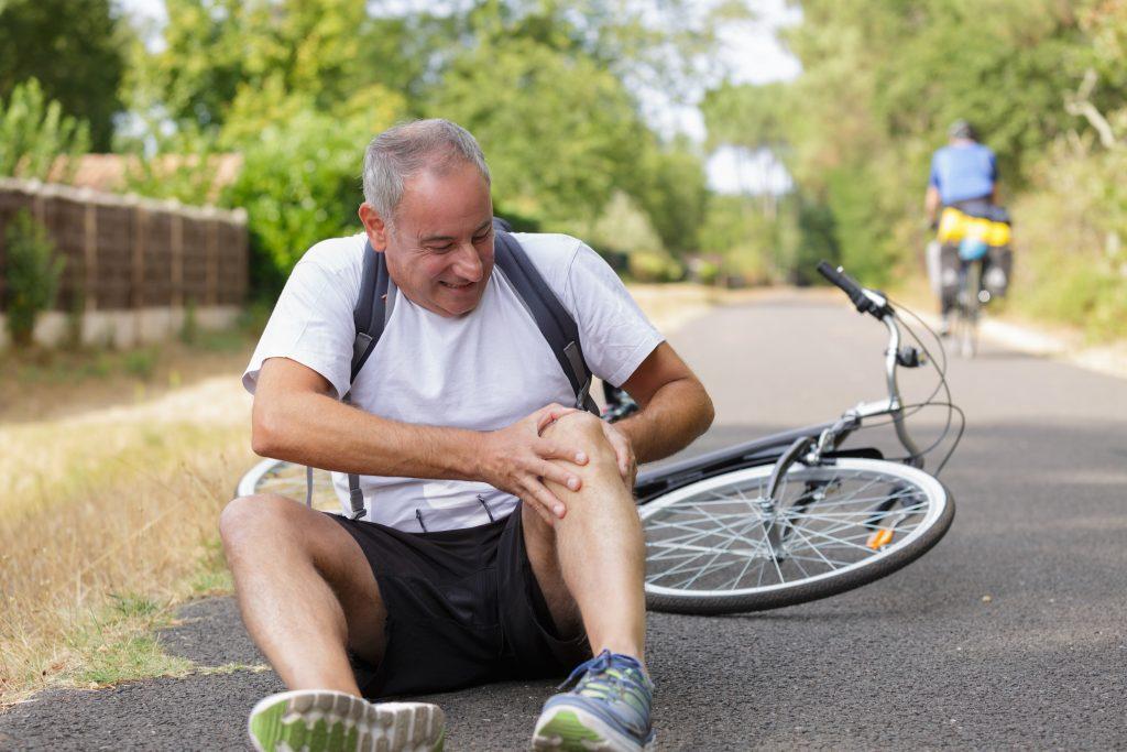 Muž v strednom veku sedí vedľa bicykla a drží sa za koleno s výrazom bolesti