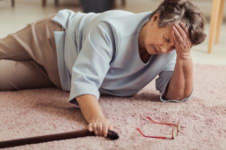 stará pani spadla a leží na zemi, držiac sa za bolestivú hlavu, vedľa nej sú spadnuté okuliare