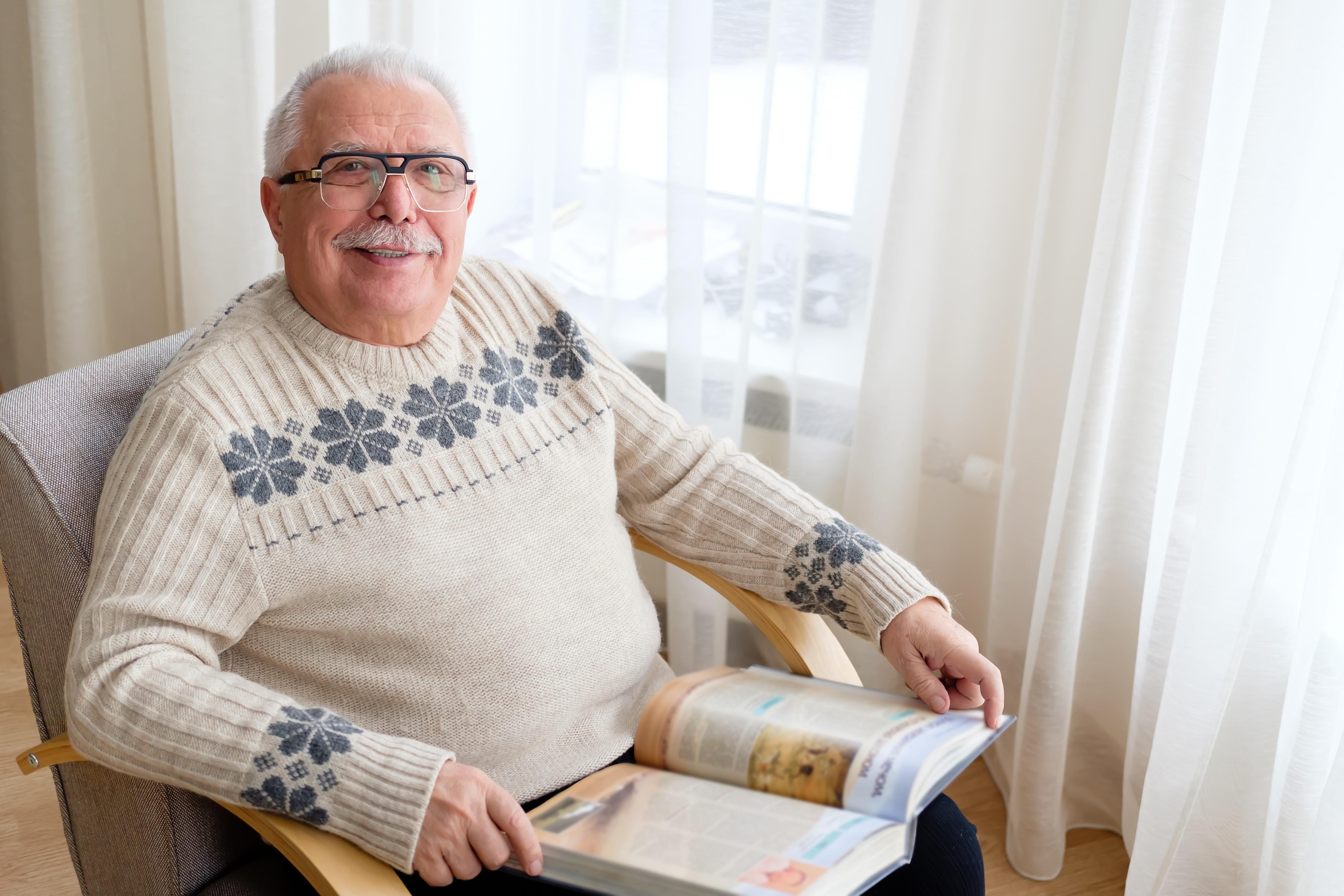 Starý pán sedí v kresle, usmieva sa do kamery a na kolenách má otvorenú knihu