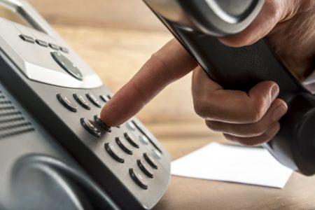 detail na ruku vytáčajúcu telefónne číslo na tlačítkovej pevnej linke