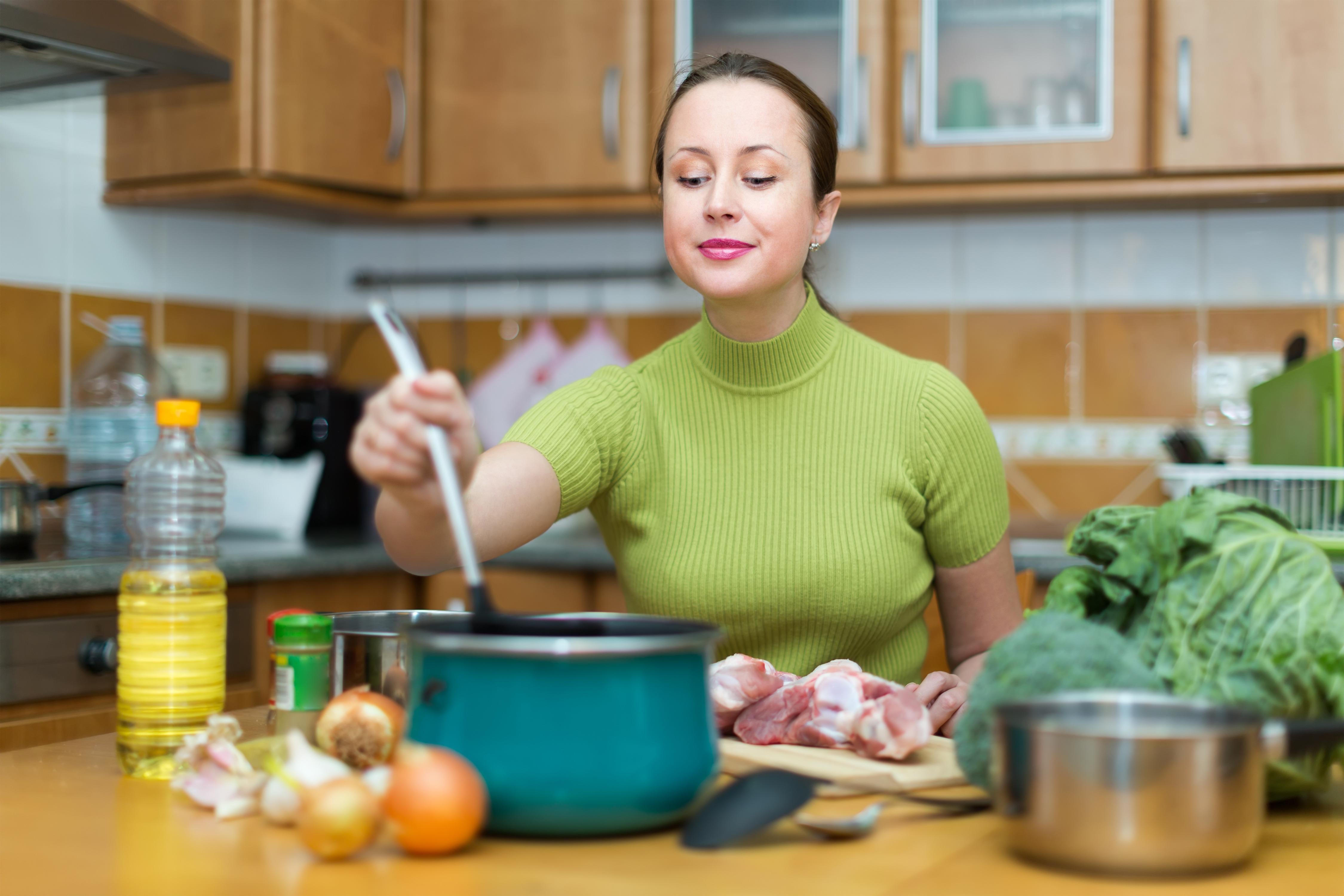 Mladá žena nazerá do hrnca pri varení, pred sebou má nakrájané mäso a pripravenú zeleninu