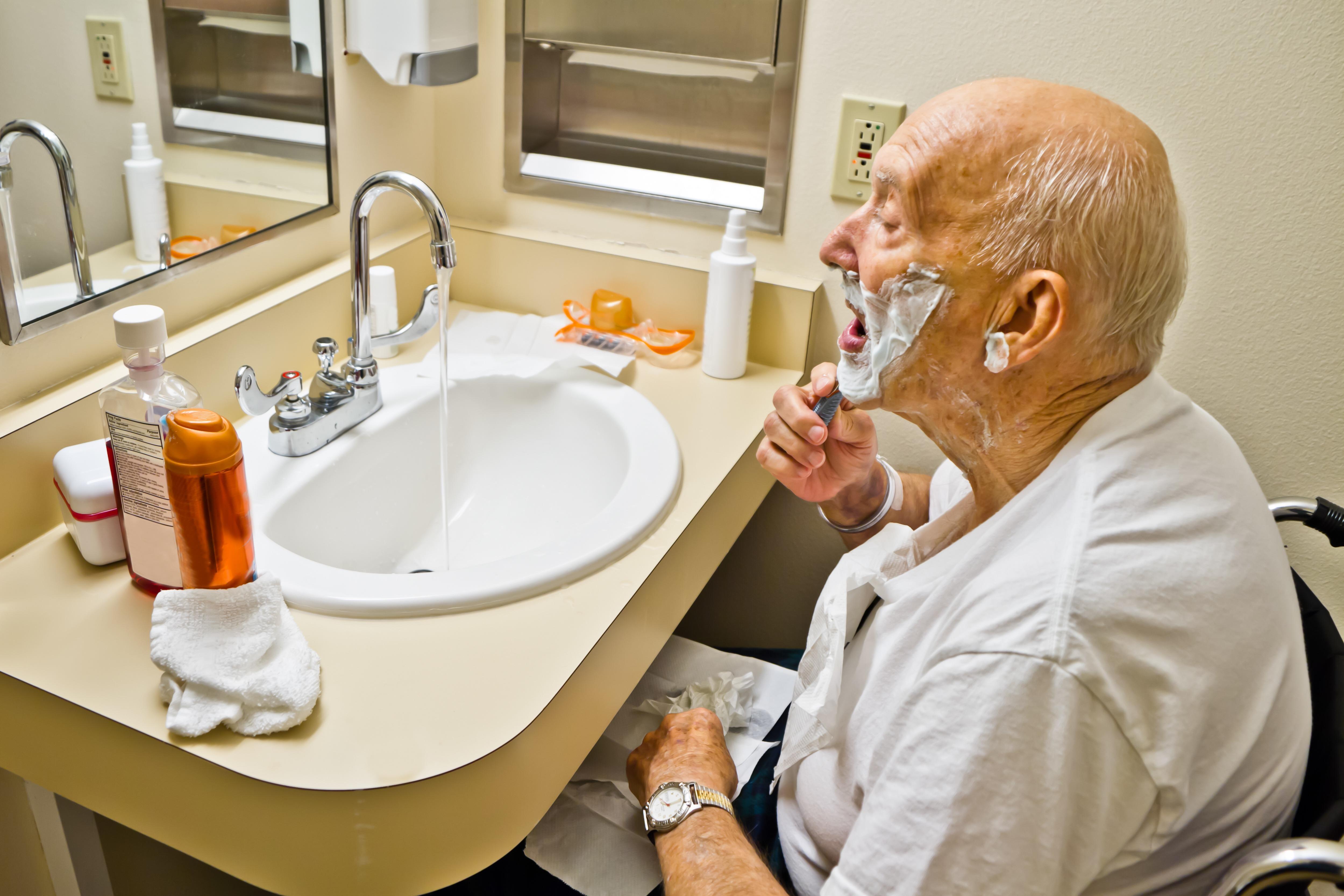 Starý muž na vozíku sedí pred umývadlom v kúpeľni a holí si tvár