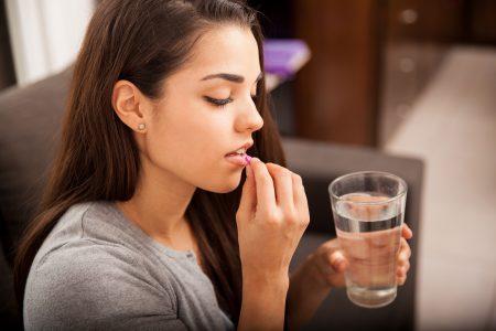 mladá žena berie antikoagulačné lieky a zapíja ich pohárom vody