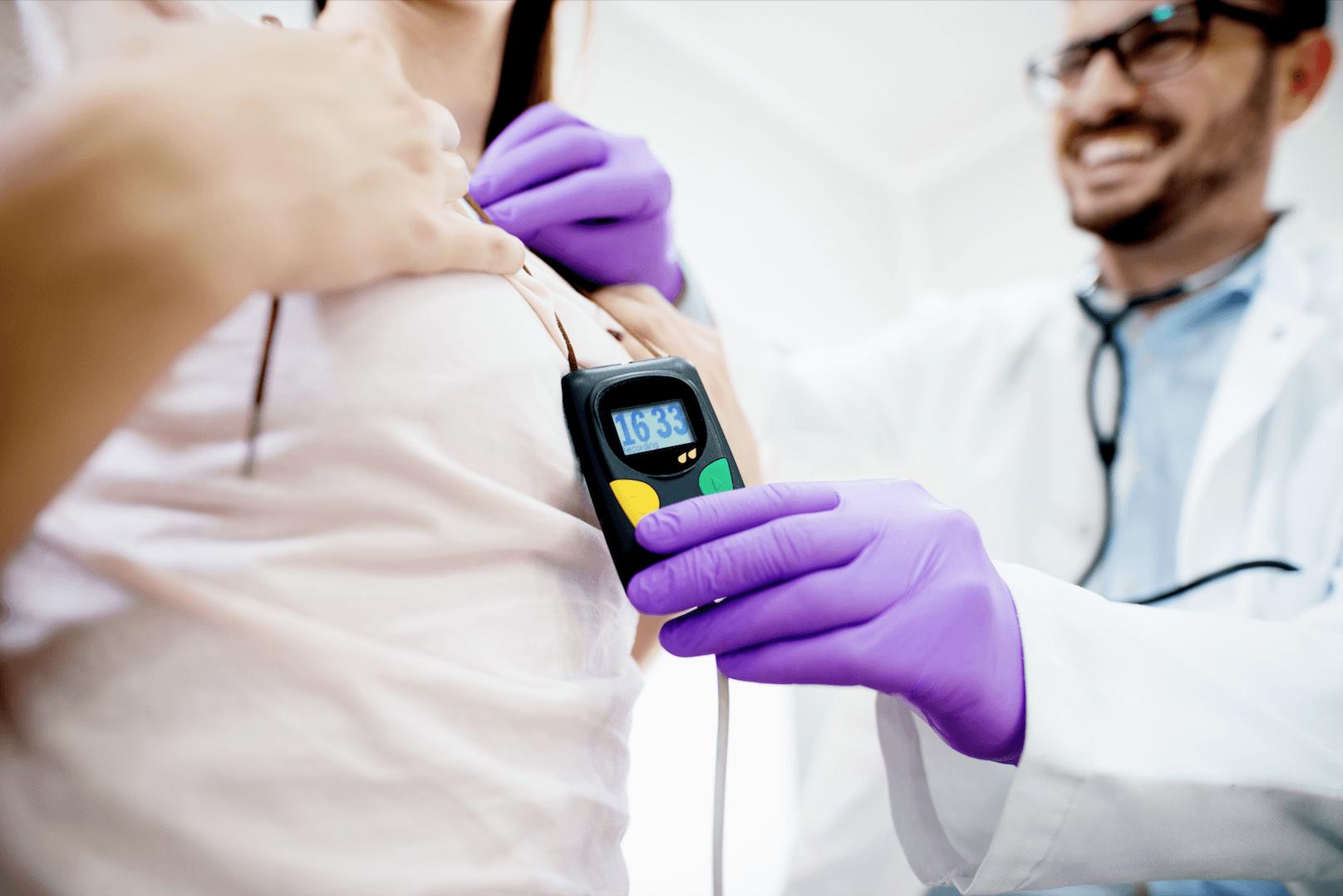 Detail na doktorovu ruku, držiaci srdcový monitor, ktorý visí pacientke na krku