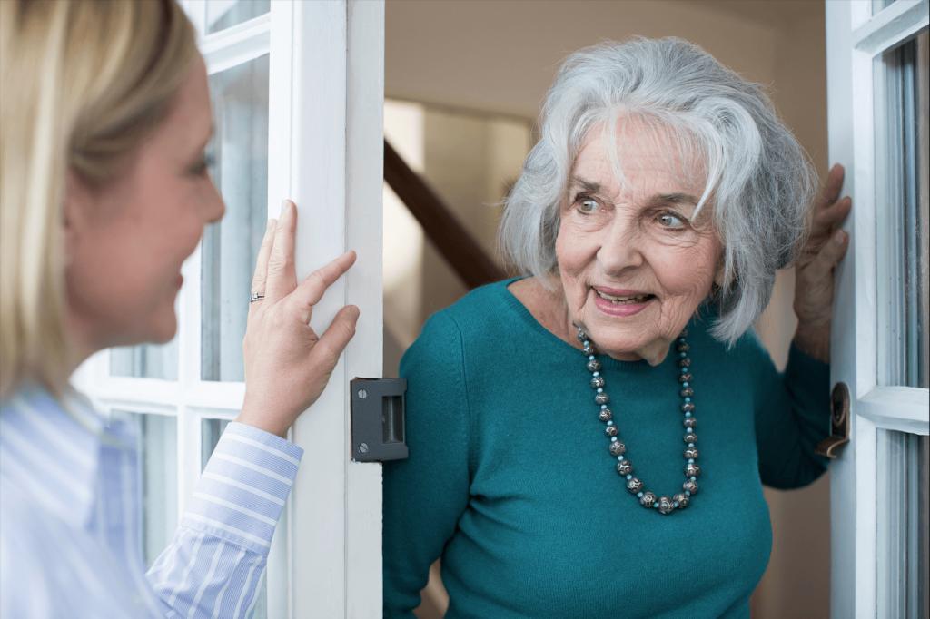 Stará pani otvára dvere návšteve - mladej pani a usmievajú sa na seba