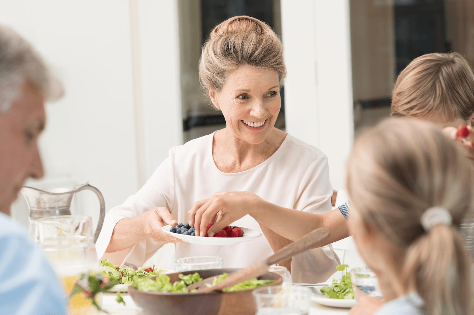 Babka sa usmieva pri spoločnom obede na ostatných členov rodiny, v ruke drží tanier s čučoriedkami a malinami