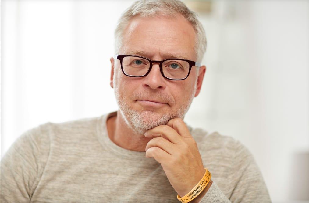 muž v strednom veku sa pozerá do kamery a premýšľa