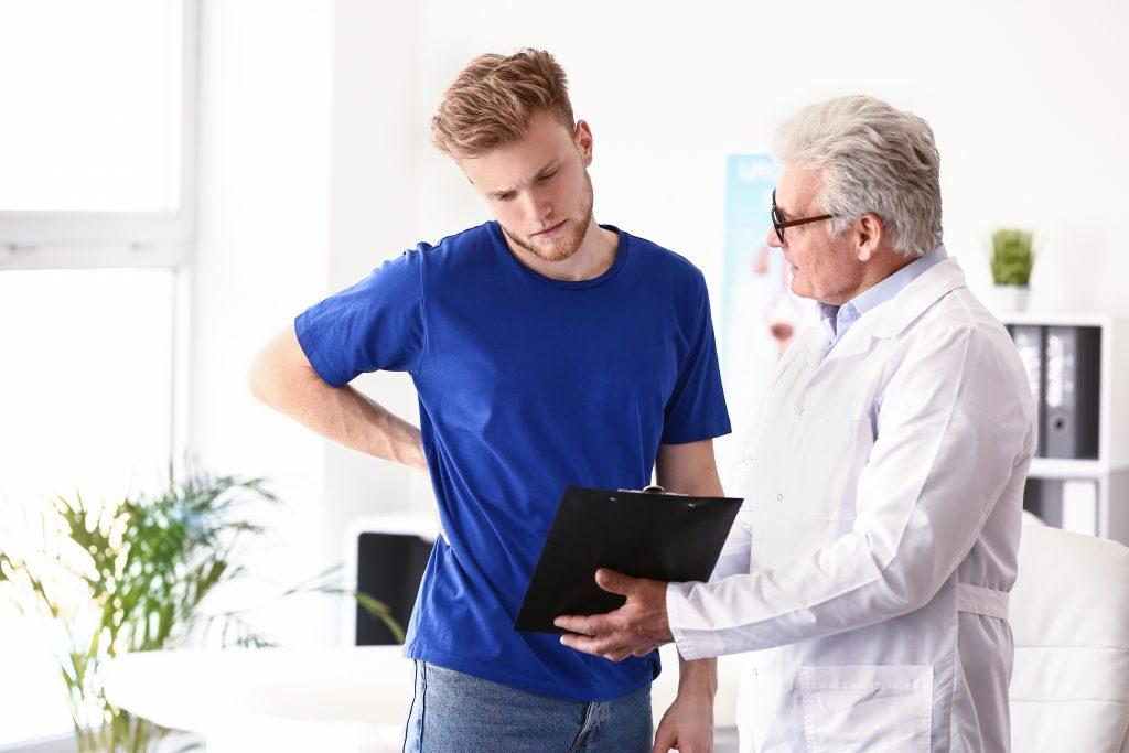 doktor ukazuje mladému mužovi výsledky, ktoré nie sú veľmi pozitívne