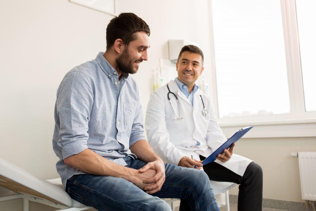 doktor s pacientom sedia na lôžku a usmievajú sa nad výsledkami