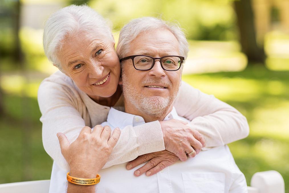 starší pár sa pozerá do kamery, žena objíma muža spoza chrbta