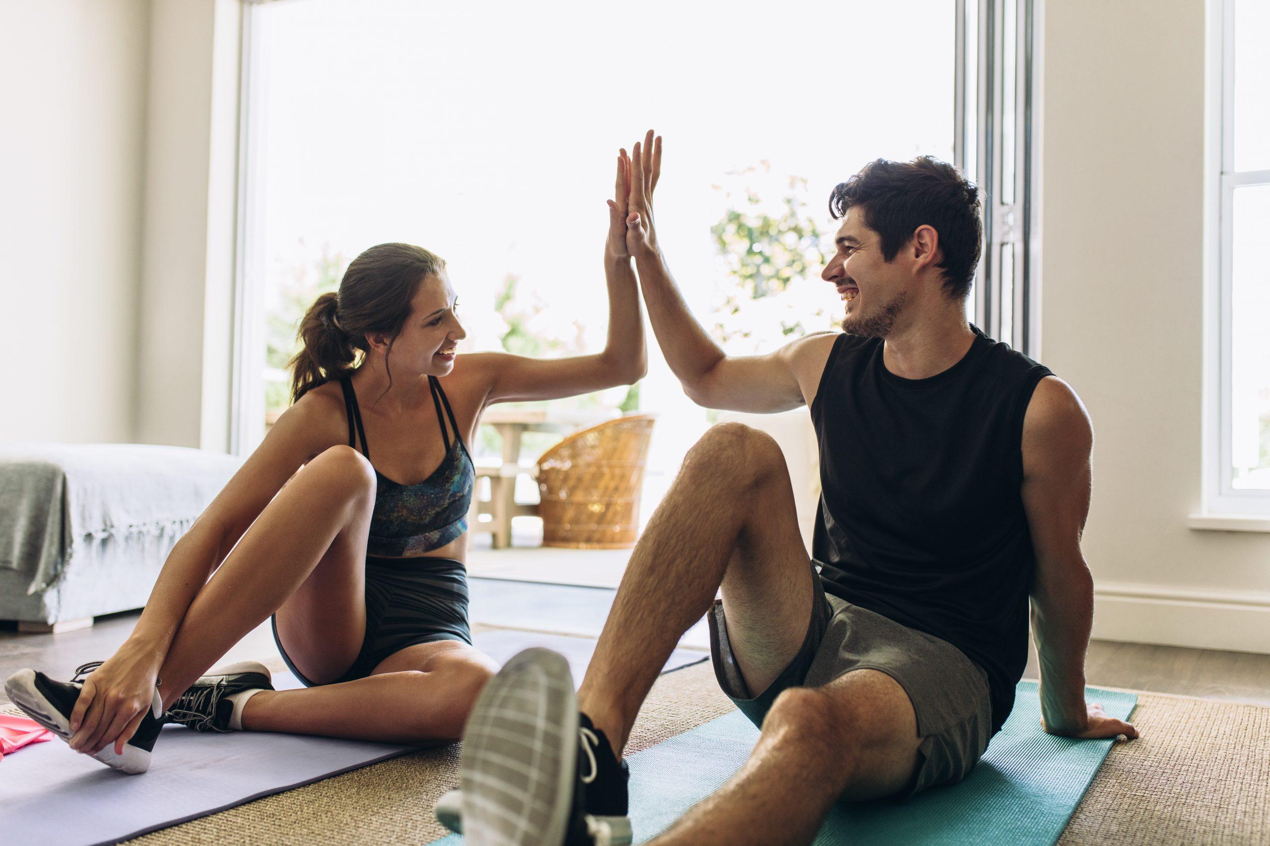 mladý muž a mladá žena si dávajú high-five po cvičení na karimatkách