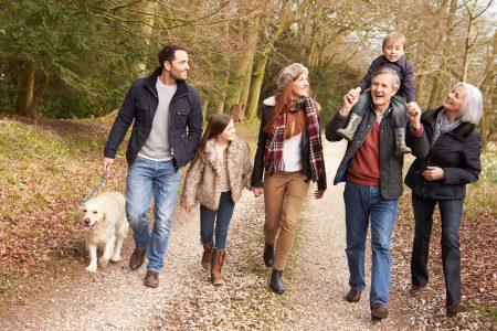 starí rodičia, rodičia, dve deti a pes si vyšli na prechádzku do jesennej prírody