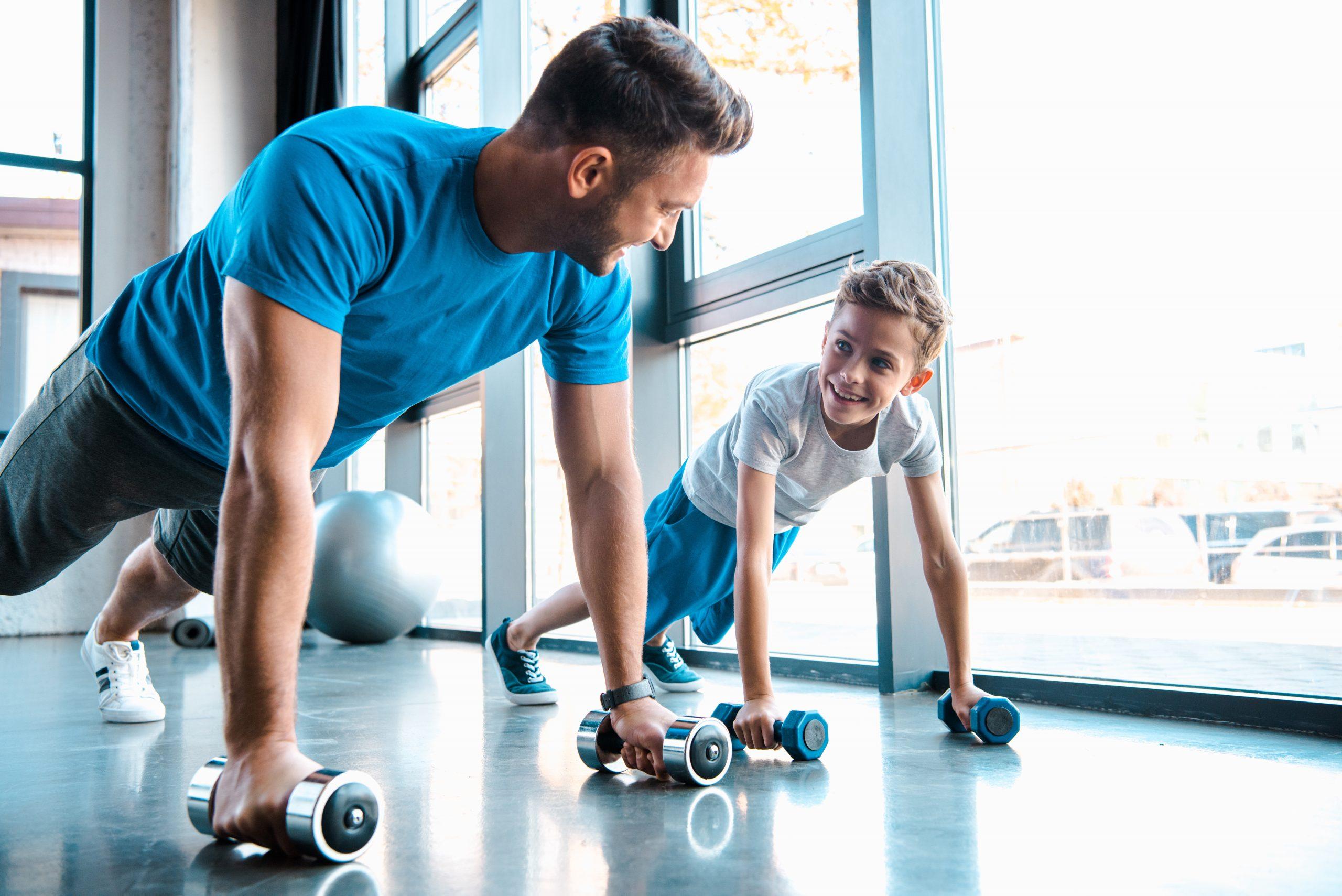 muž cvičí so svojím synom v posilňovni