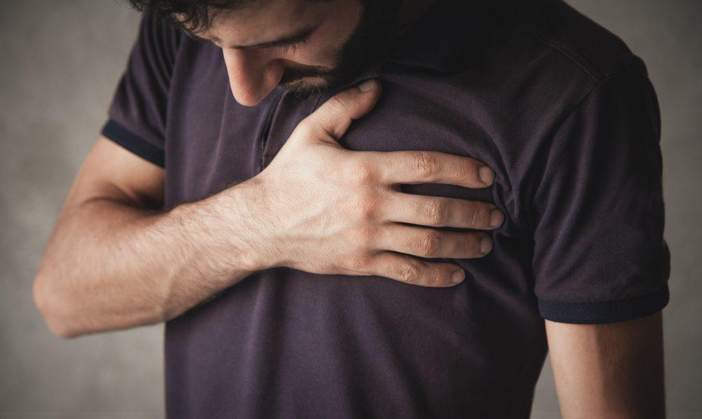 mladý muž sa pozerá do zeme a drží sa za srdce