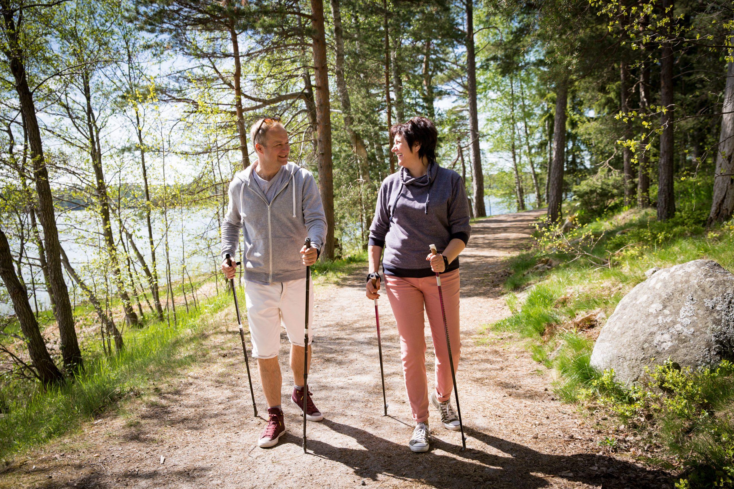 starší pár s palicami na chodenie je na prechádzke prírodou