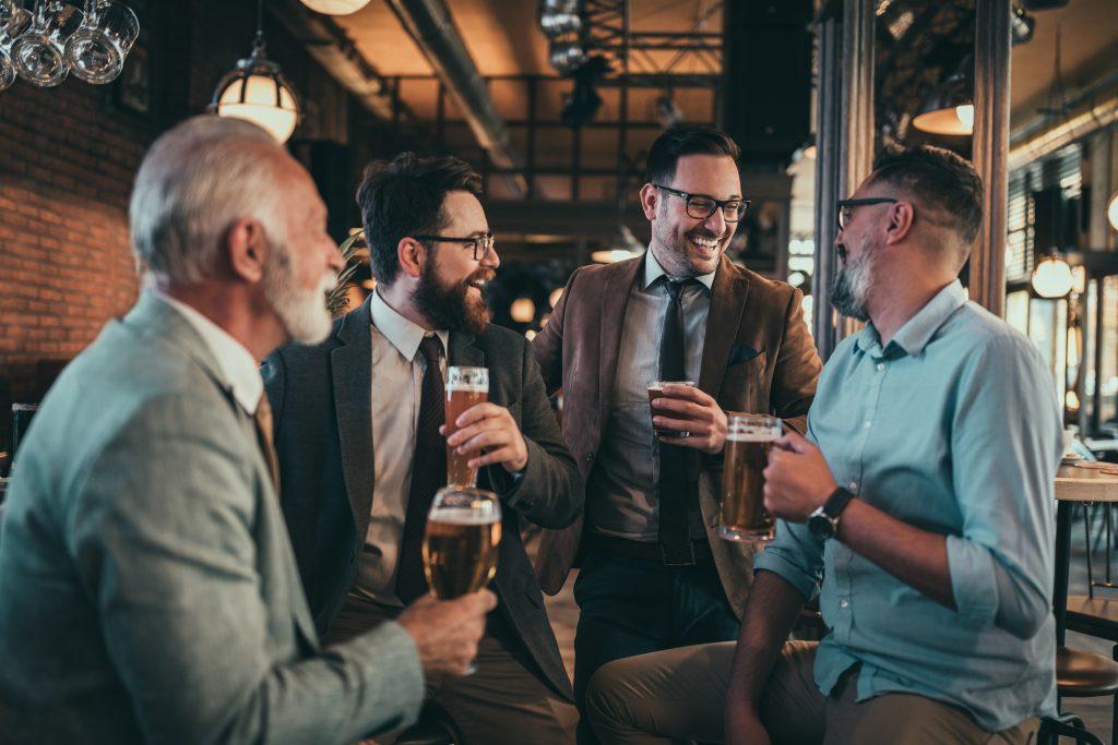 Skupinka štyroch mužov sedí v bare, pije pivo a zabáva sa