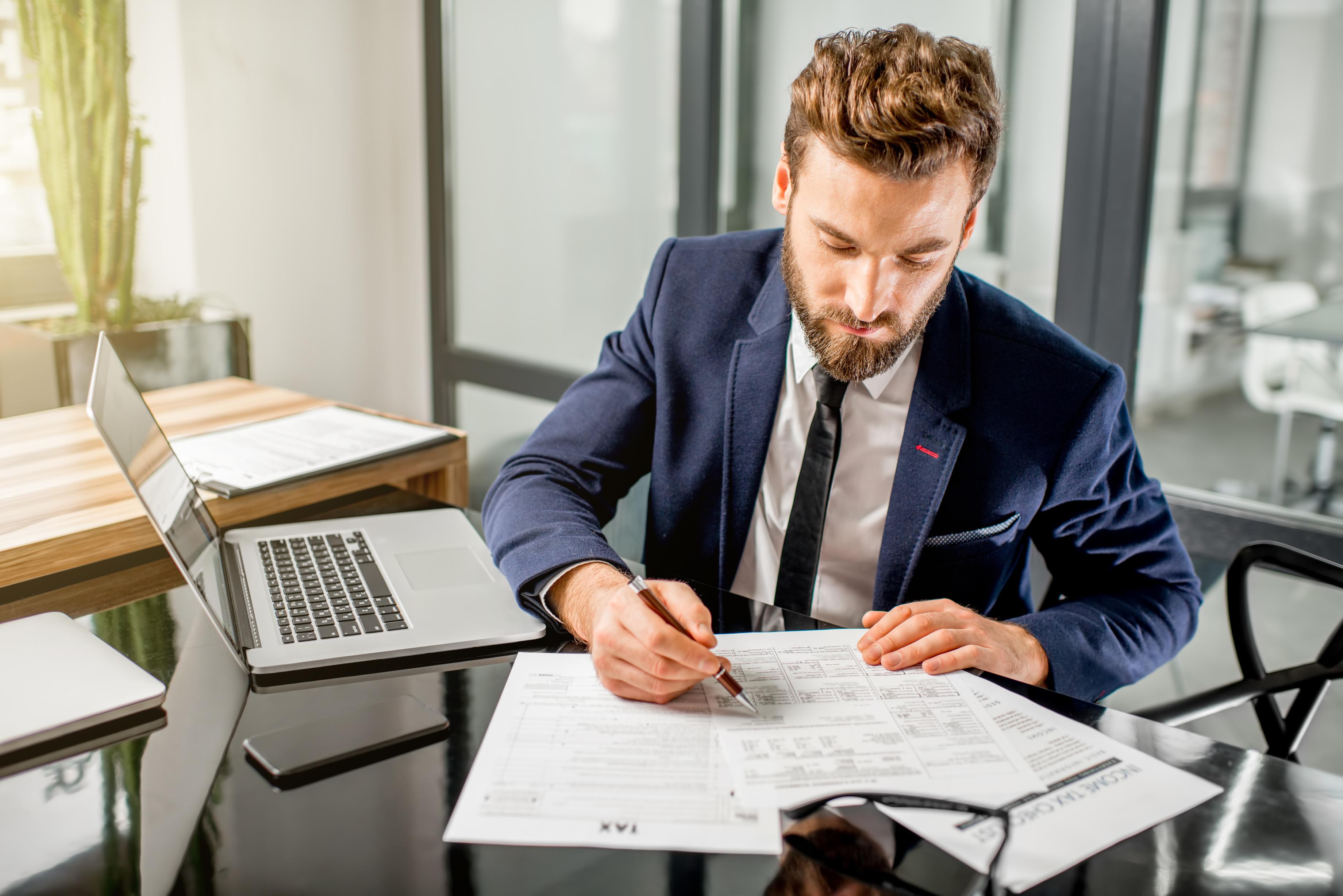 Mladý muž sedí za stolom s notebookom a pozerá sa do papierov