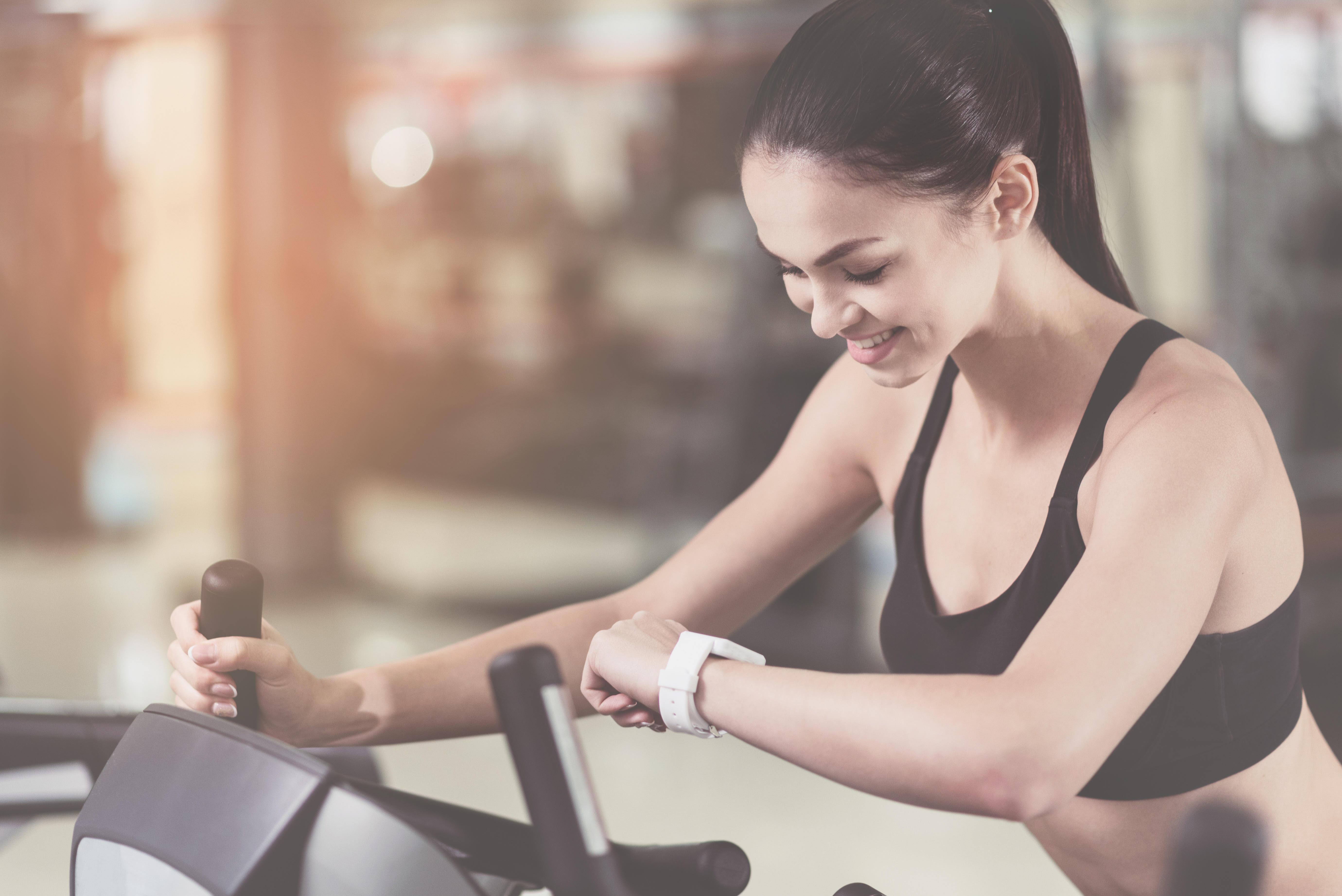 Mladá žena si kontroluje pulz pri cvičení na kardio prístroji