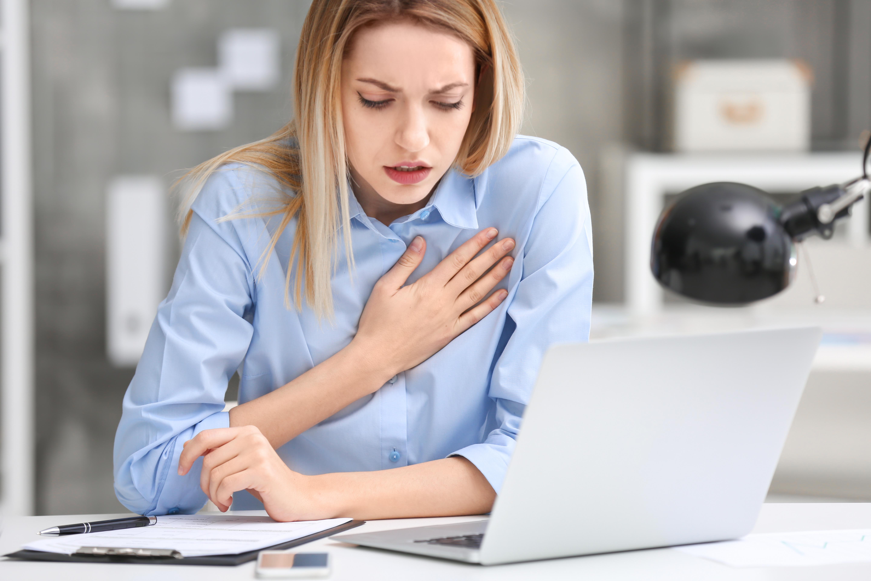 Mladá žena za notebookom sa s bolesťou chytá za srdce