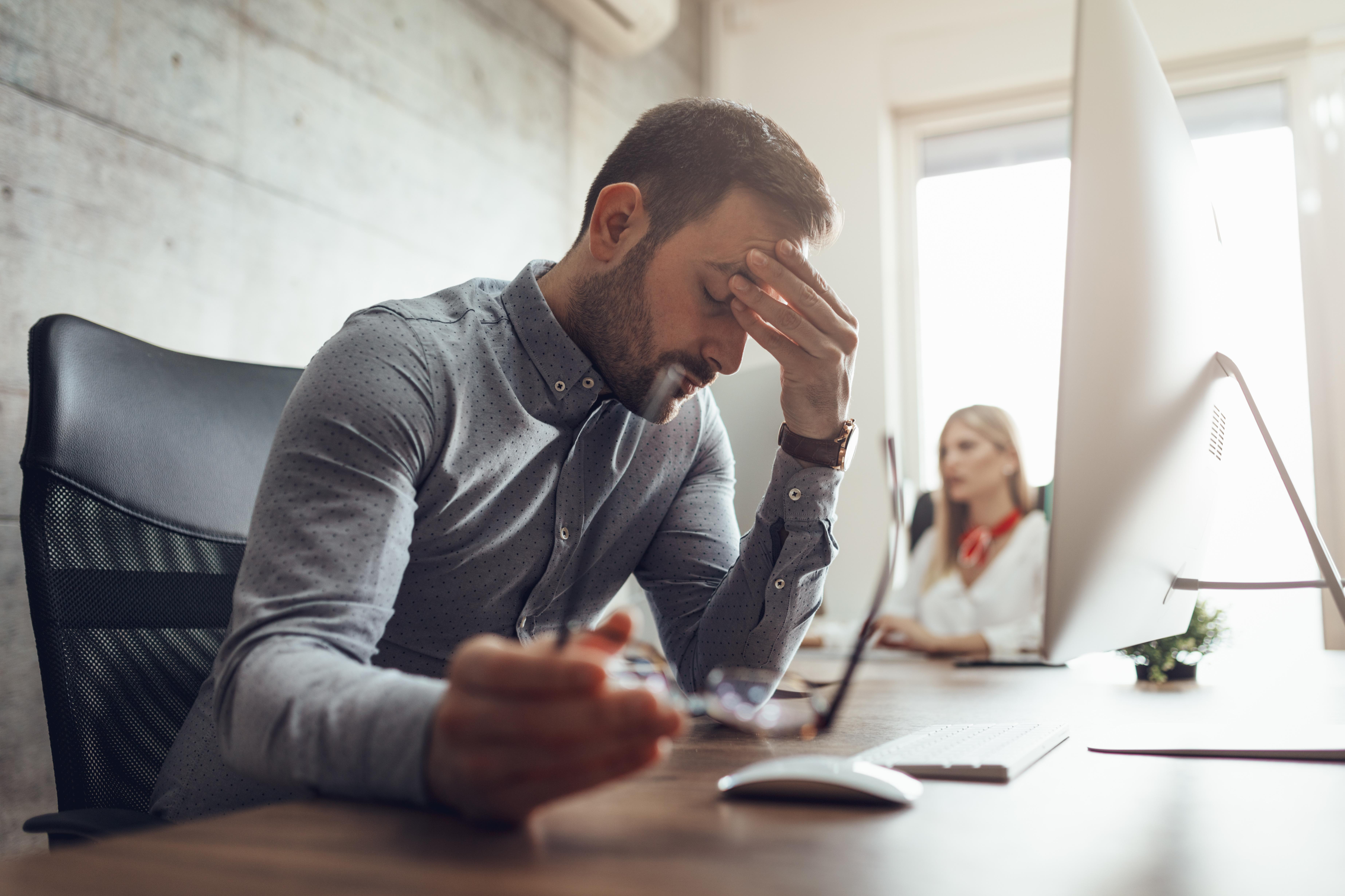 Mladý muž sa drží za bolestivé čelo v práci pred monitorom