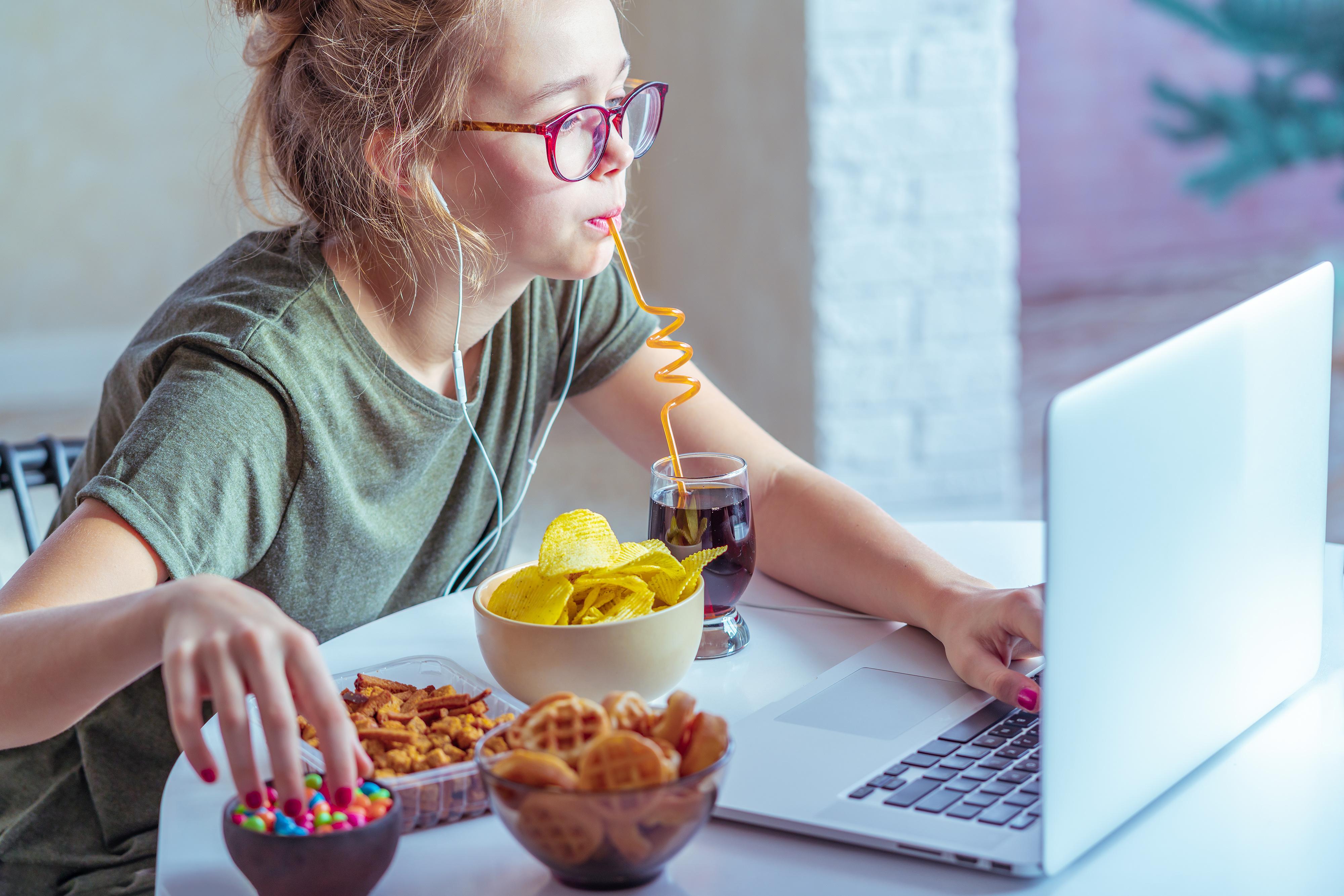 Mladé dievča pozerá do notebooku, pije colu cez slamku a pred sebou má nezdravé pochutiny