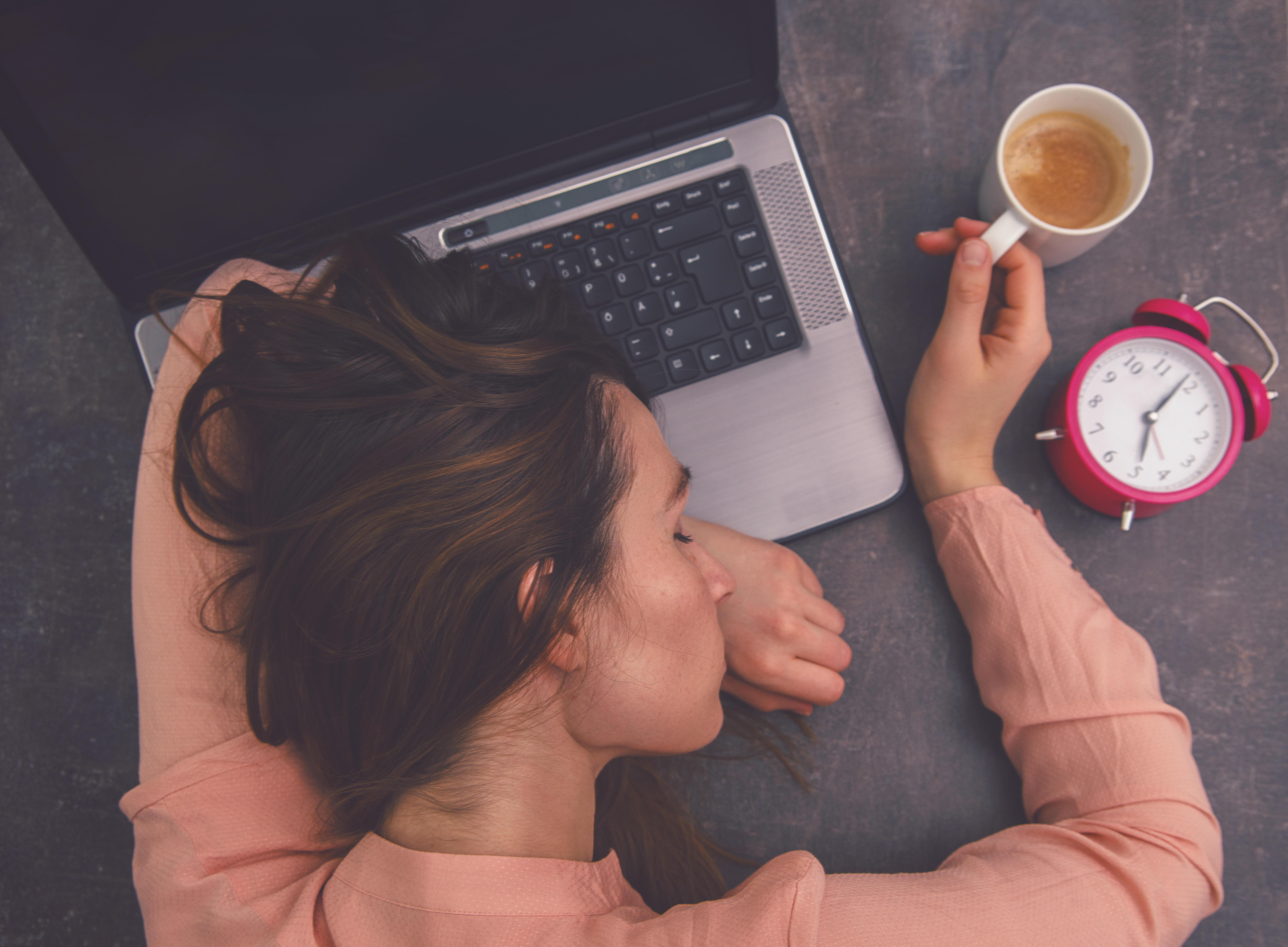 mladá žena so šálkou kávy v ruke spí na notebooku, vedľa nej je budík ukazujúci päť hodín