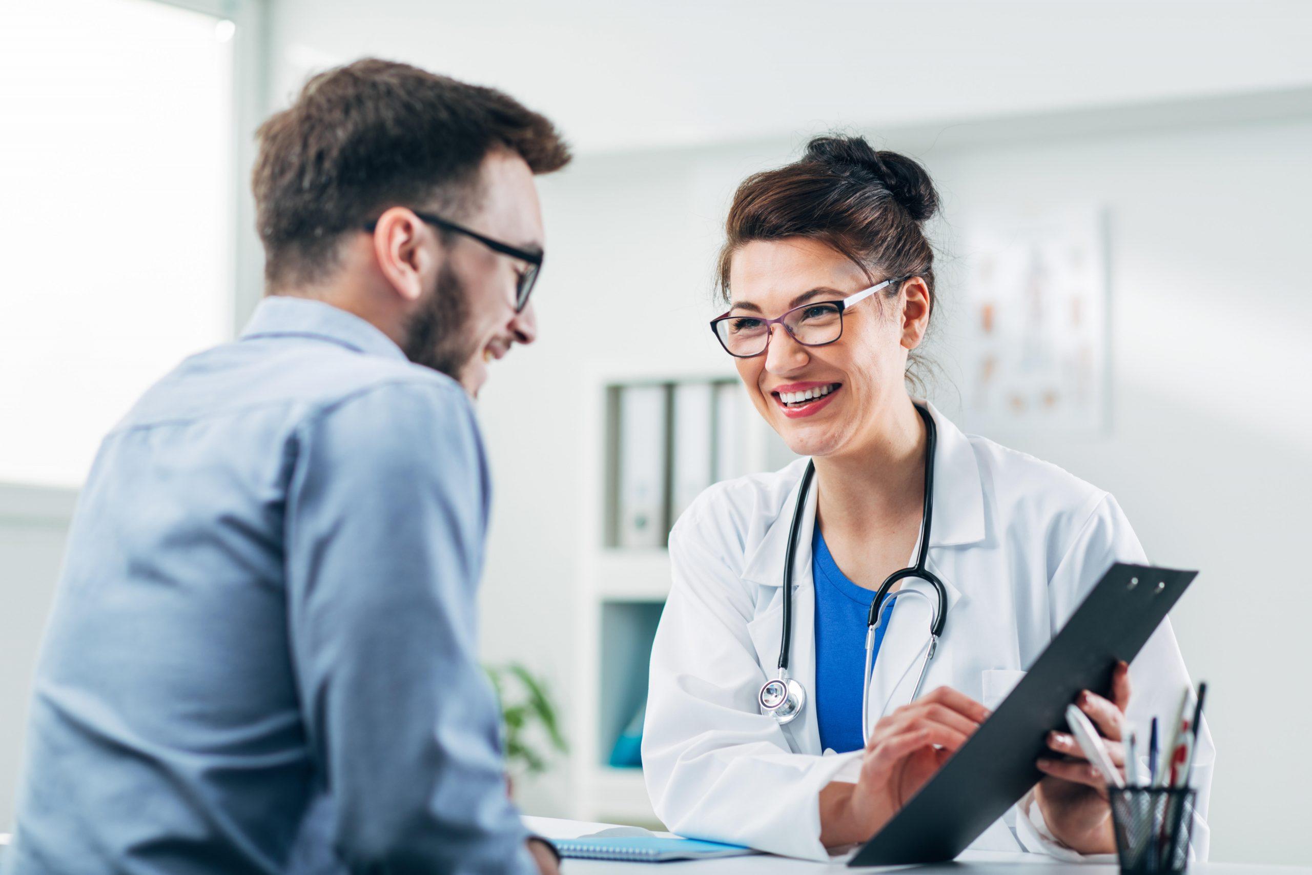 doktorka s úsmevom ukazuje výsledky svojmu pacientovi