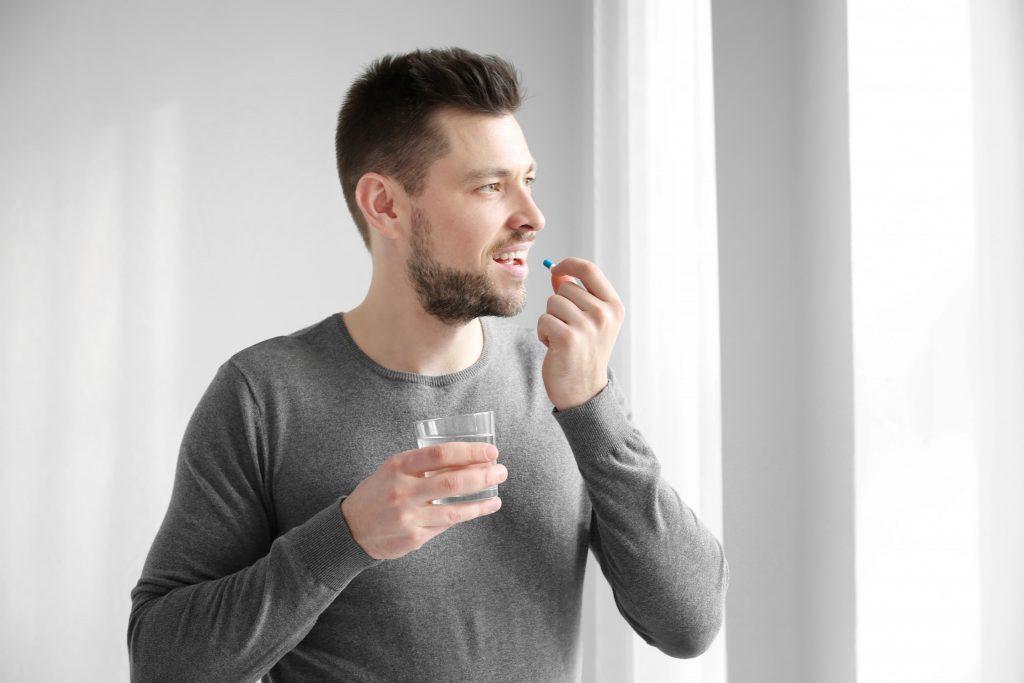 muž si dáva tabletku a zapíja ju pohárom vody
