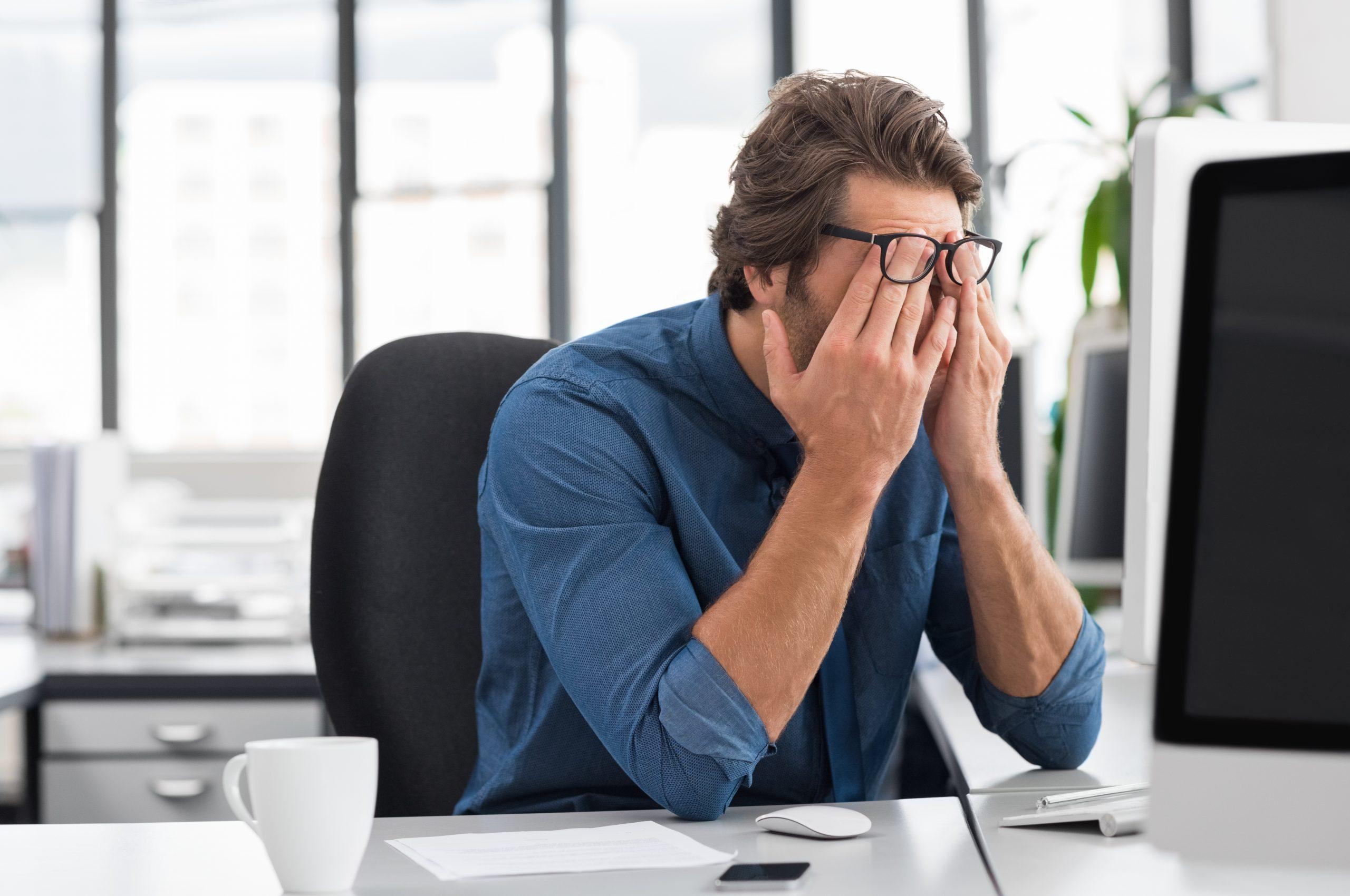 mladý muž si šúcha oči od únavy pred monitorom