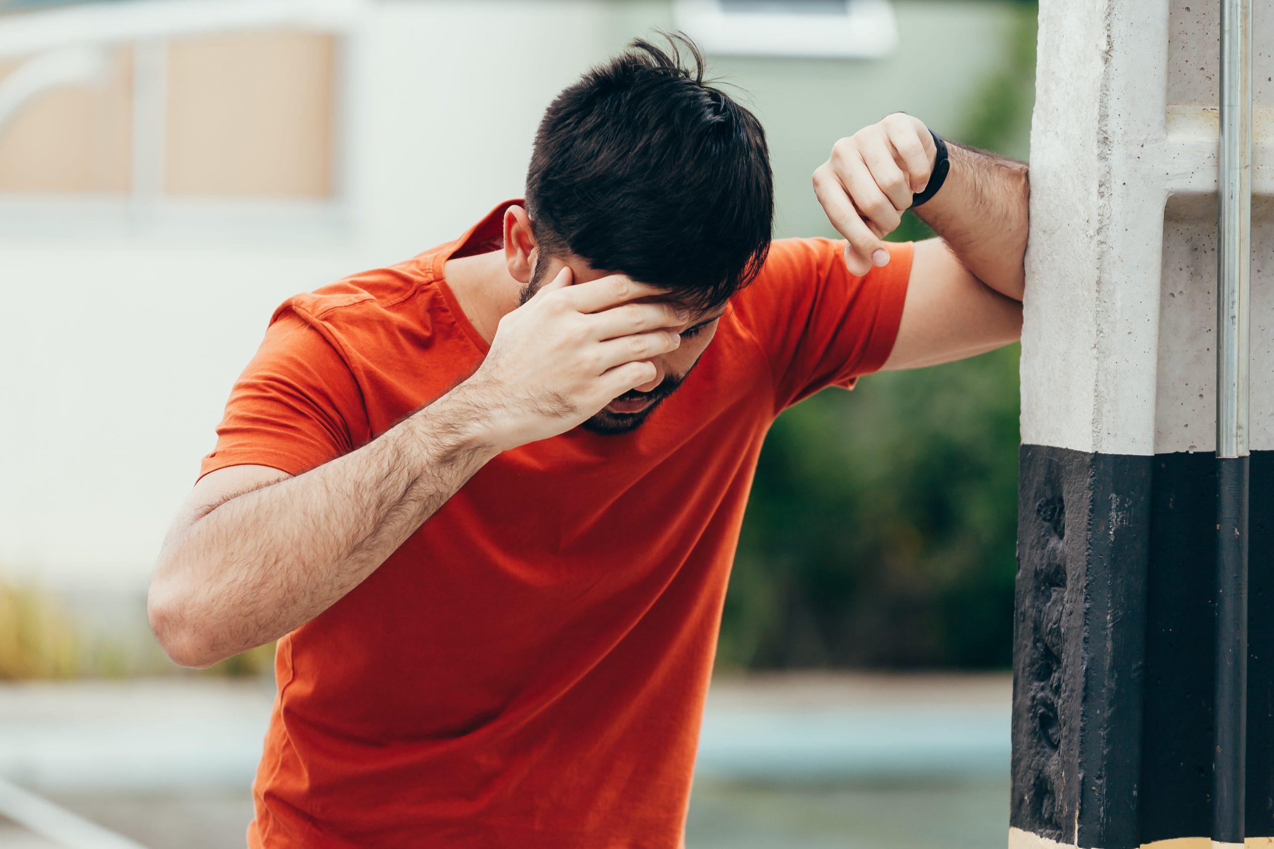mladý muž sa opiera o múr a chytá za bolestivú hlavu