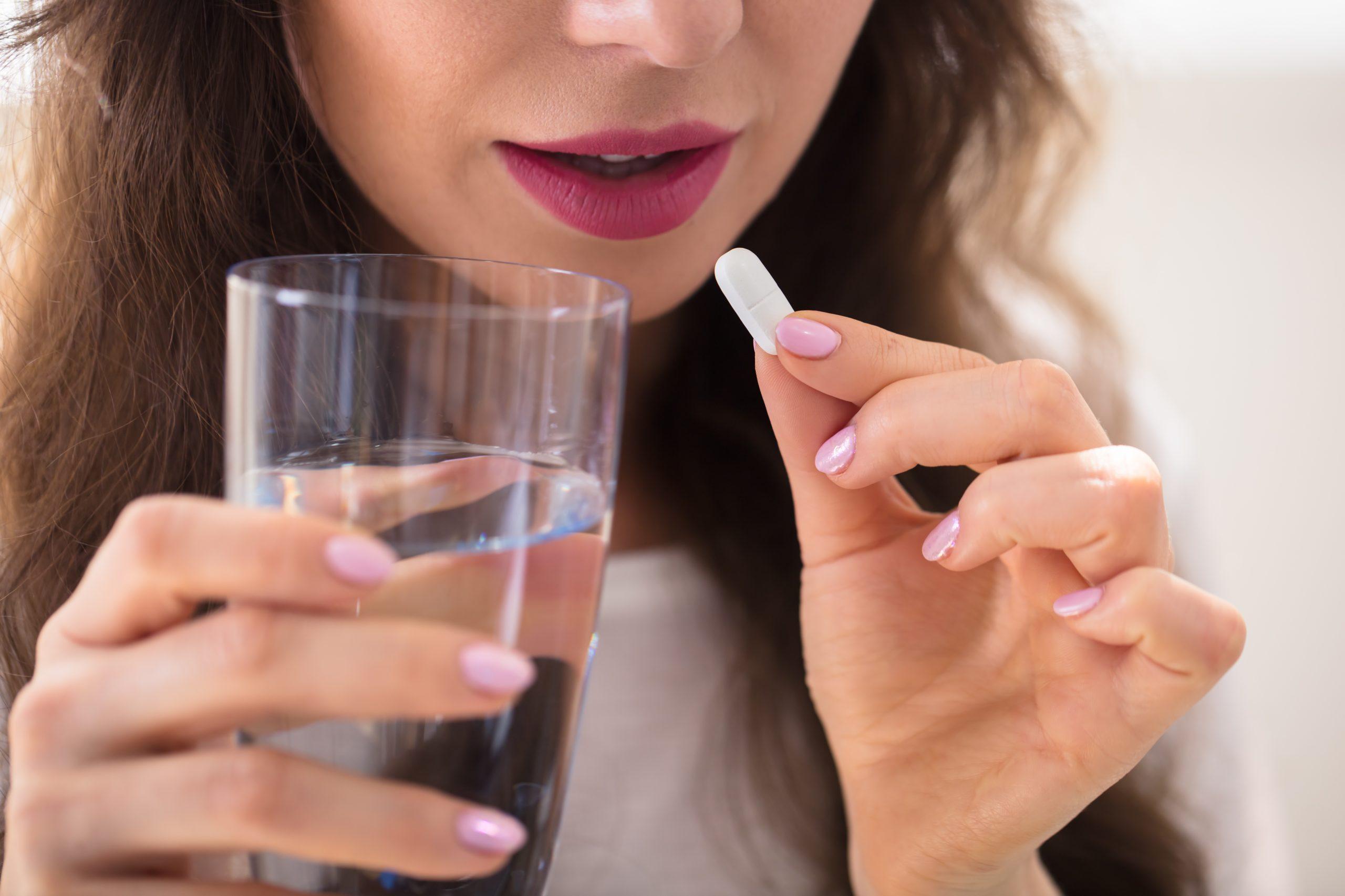 mladá žena si dáva do úst tabletku a zapíja pohárom vody