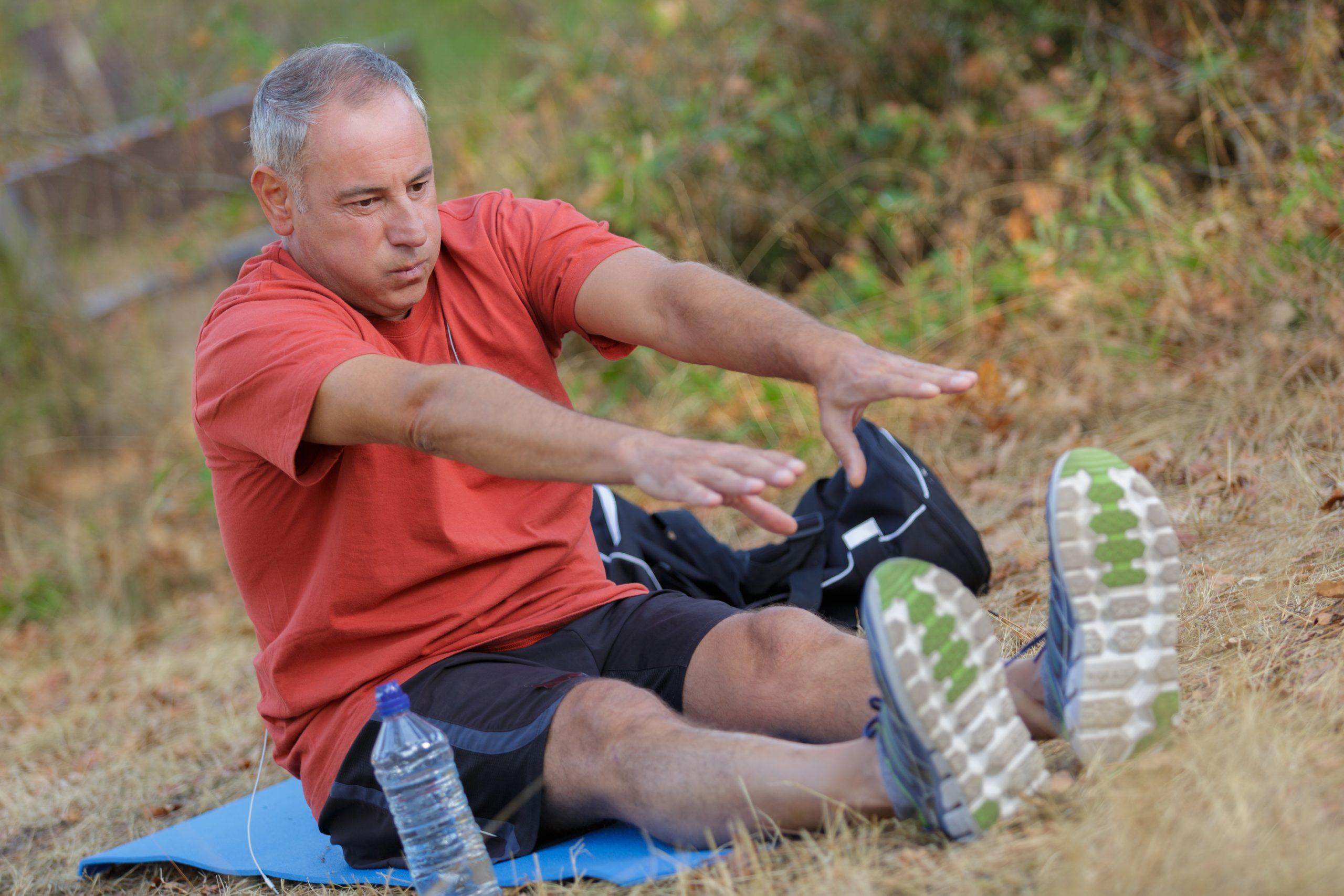 muž cvičí a naťahuje sa za chodidlami