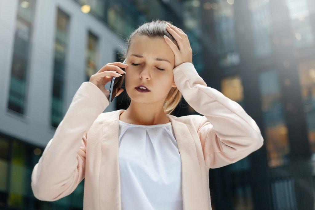 mladá žena drží telefón pri uchu a druhou rukou sa drží za bolestivú hlavu