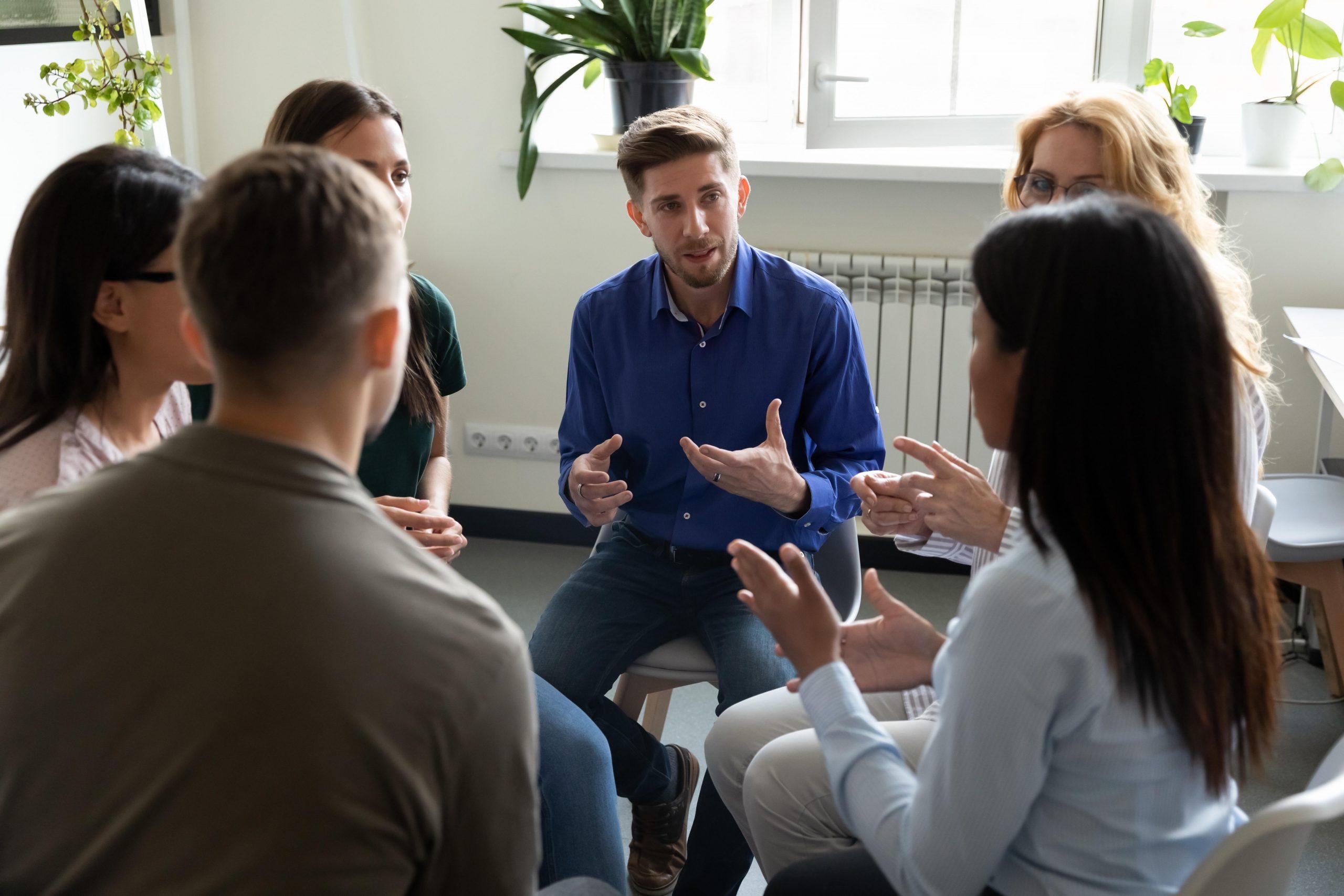 ľudia sediaci v kruhu, skupinová terapia