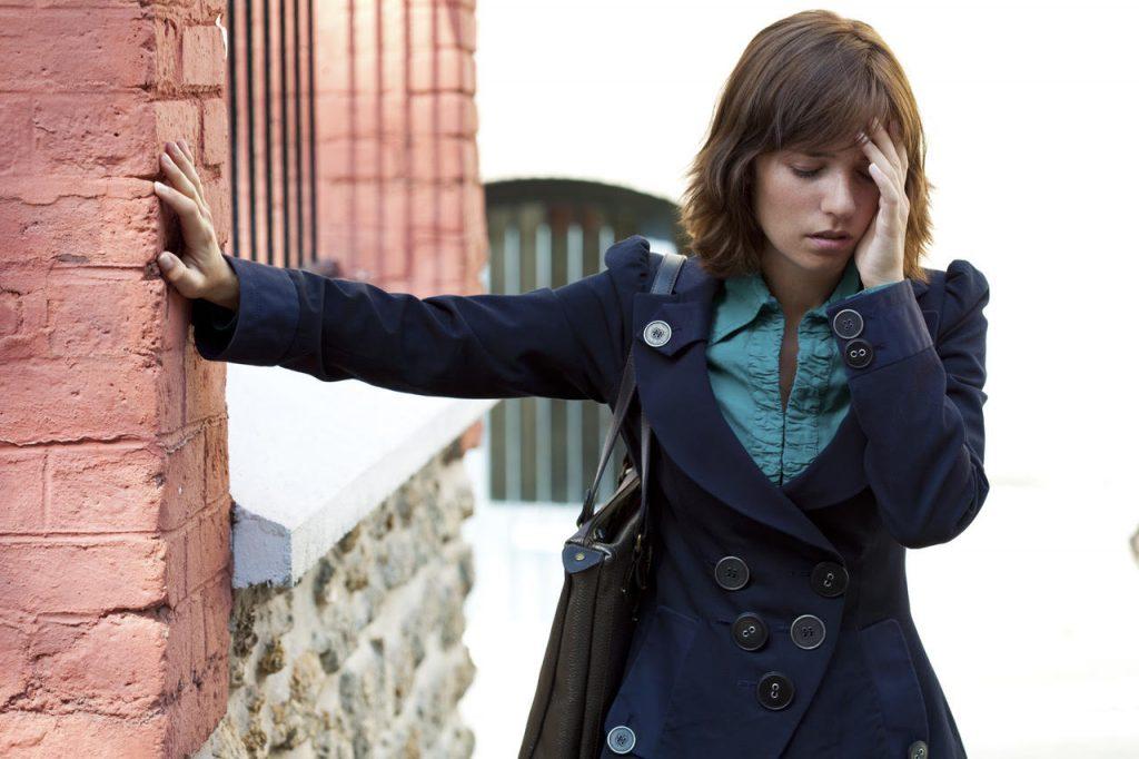 mladá žena sa opiera o stenu a drží za bolestivú hlavu