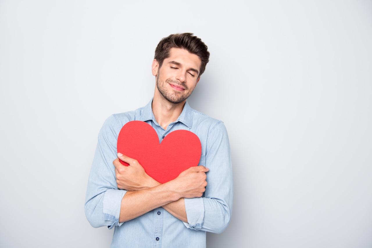 mladý muž drží v náručí predmet v tvare červeného srdca