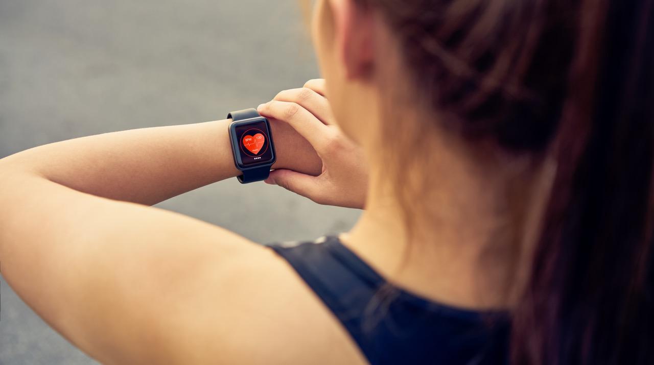 mladá žena si pri športe kontroluje tep na chytrých hodinkách