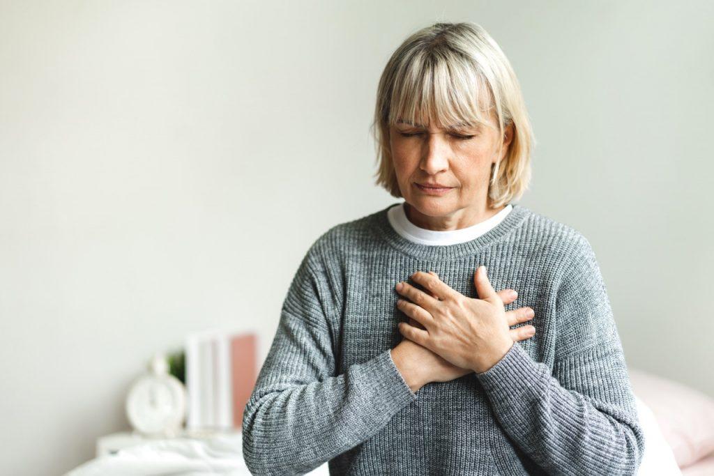 žena sa drží za srdce a cíti bolesť