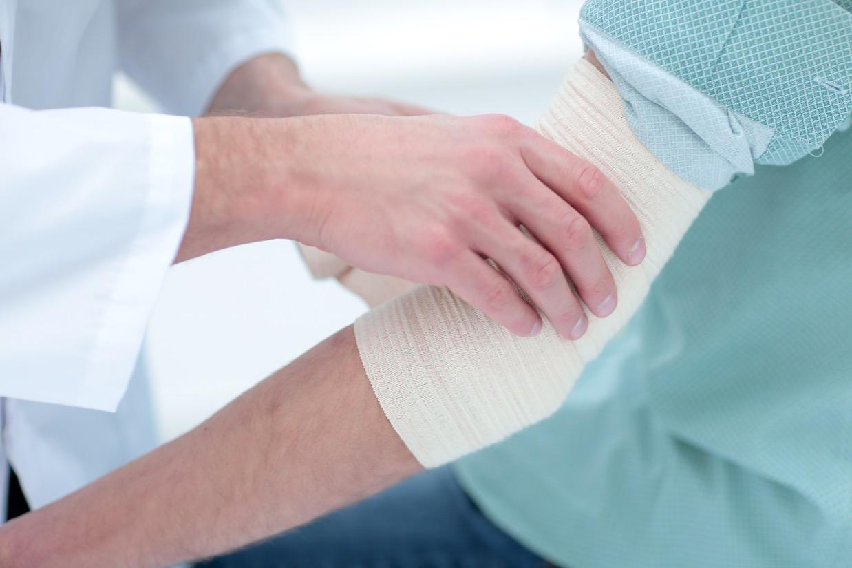 doktor ošetruje obväzom pacientovu ruku