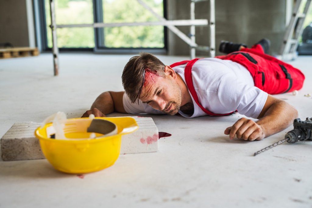 zranený muž po pracovnom úraze leží na zemi a krváca z hlavy