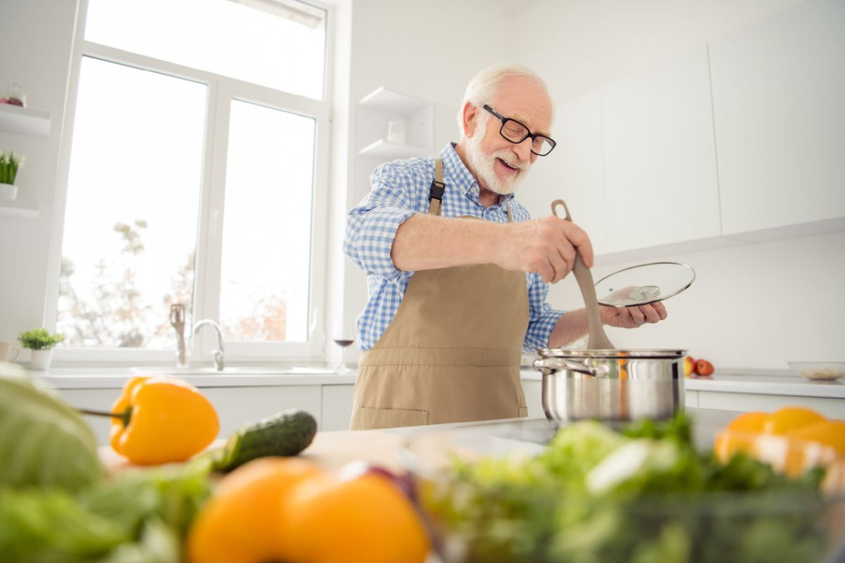 seniorný pán s radosťou varí zeleninové jedlo